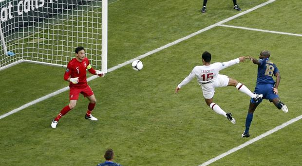 England's Joleon Lescott (centre) scores the opening goal past France goalkeeper Hugo Lloris (left) during the Euro 2012 soccer championship Group D match between France and England in Donetsk, Ukraine