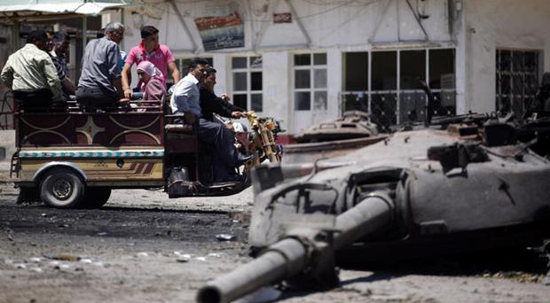 Syrians look at a destroyed military tank at the northern town of Ariha, on the outskirts of Idlib, Syria
