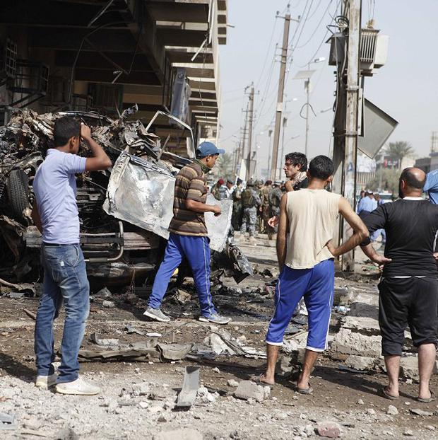People and security forces inspect the scene of a car bomb attack in the Karrada neighborhood of Baghdad, Iraq (AP)