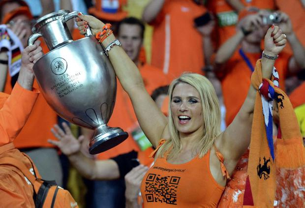 A Dutch fan holds a replica UEFA trophy during the Euro 2012 soccer championship Group B match between the Netherlands and Germany in Kharkiv, Ukraine, Wednesday, June 13, 2012