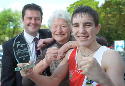 Michael Conlan receives his Mary Peters Trust Outstanding Athlete Award from Mary, President of the Trust and Richard Rodgers, Managing Director of Carillion Energy Services