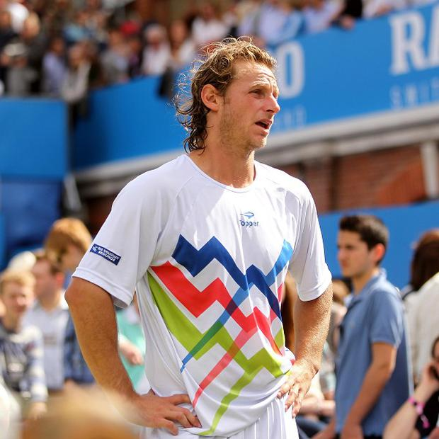David Nalbandian stands dejected following his disqualification from the Aegon Championships final after he kicked an advertising board