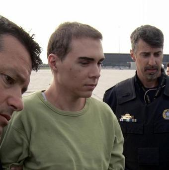 Luka Magnotta, centre, is taken by police from a Canadian military plane to a waiting van in Mirabel, Quebec (AP/Montreal Police)