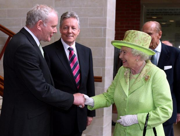 Queen Elizabeth II shakes hands with Northern Ireland Deputy First Minister and former IRA commander Martin McGuinness watched by First minister Peter Robinson (centre) at the Lyric Theatre in Belfast