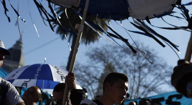People bang drums as they attend a demonstration at Plaza de Mayo in Buenos Aires, Argentina (AP)