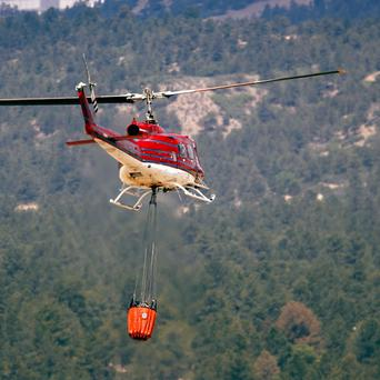 A helicopter takes off to combat wildfires as they roll through housing subdivisions in the mountains north and west of Colorado Springs (AP)