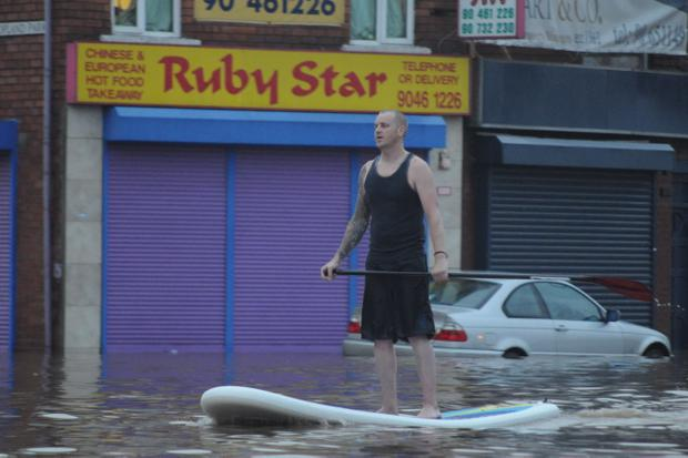 East Belfast surfboard superhero rescues flood victims. Image submitted by Conor Dunn