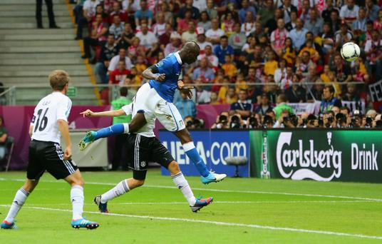 WARSAW, POLAND - JUNE 28: Mario Balotelli (L) of Italy jumps next to Holger Badstuber of Germany to score the opening goal during the UEFA EURO 2012 semi final match between Germany and Italy at National Stadium on June 28, 2012 in Warsaw, Poland. (Photo by Alex Grimm/Getty Images)