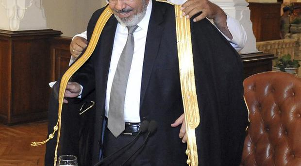 Egypt's President-elect Mohammed Morsi is given a traditional robe during a meeting with political party representatives (AP/Egyptian Presidency)