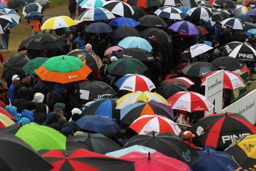 PORTRUSH, NORTHERN IRELAND - JUNE 30: Fans in the rain, some holding umbrellas wait on the 1st hole tee during Day Three of the 2012 Irish Open held on the Dunluce Links at Royal Portrush Golf Club on June 30, 2012 in Portrush, Northern Ireland. (Photo by Dean Mouhtaropoulos/Getty Images)