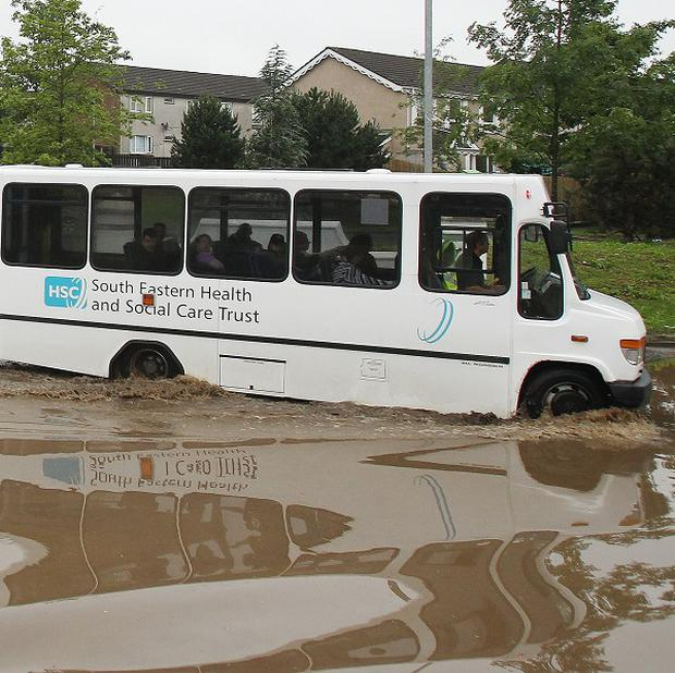 A bus driver drives through flood water in the Twinbrook estate in Lisburn