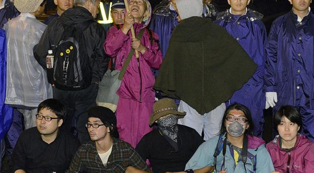 People sit in protest on a road near the entrance to the Ohi nuclear power plan in Ohi town, Fukui, western Japan (AP)