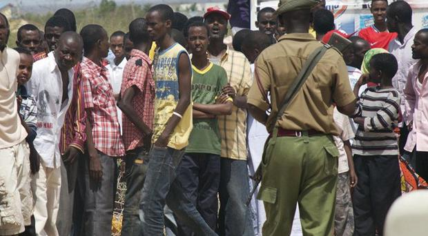 Members of the Kenyan security forces keep onlookers back from the scene outside the African Inland Church in Garissa (AP)