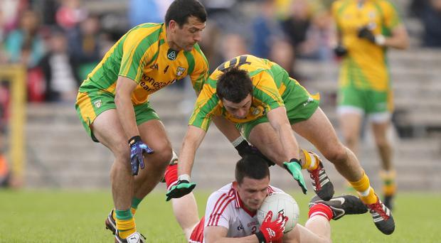 Tyrone's Aidan McCory is tackled by Frank McGylnn and David Walsh of Donegal