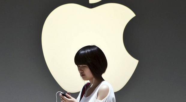 A woman walks outside an Apple store in Shanghai, China (AP)