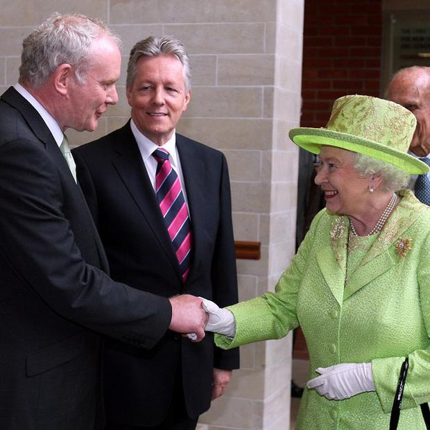 The Queen shakes hands with Northern Ireland's Deputy First Minister Martin McGuinness watched by First Minister Peter Robinson