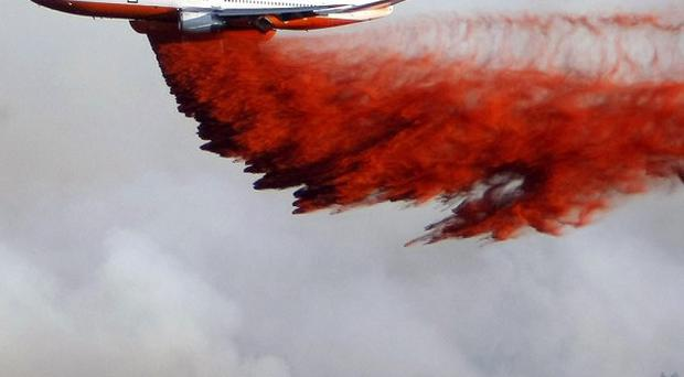 Firefighting planes drop flame retardant chemicals to stop wildfires from spreading (AP)