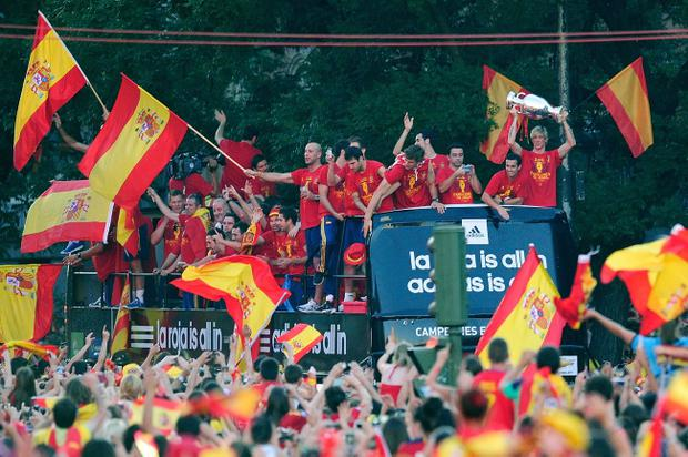 MADRID, SPAIN - JULY 02: Fernando Torres (R) of Spain holds the UEFA EURO 2012 trophy aloft while celebrating with fellow players as they parade the UEFA EURO 2012 trophy on a double-decker bus on July 2, 2012 in Madrid, Spain. Spain beat Italy 4-0 in the UEFA EURO 2012 final match in Kiev, Ukraine, on July 1, 2012. (Photo by Denis Doyle/Getty Images)