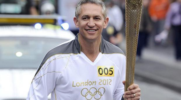Gary Lineker carries the Olympic Flame on the Torch Relay leg through Leicester (Locog/PA)