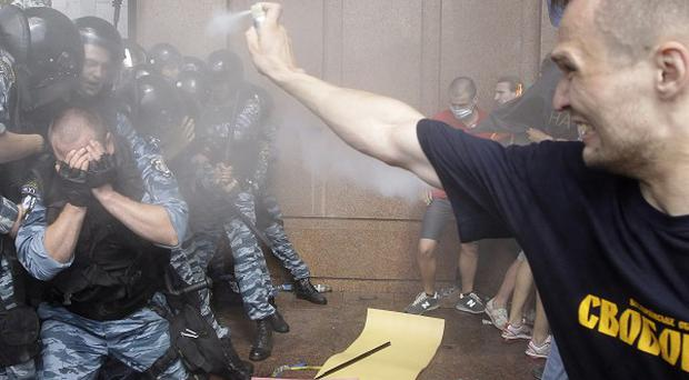 A protester sprays Ukranian riot police with tear gas during clashes over a new law promoting the Russian language (AP)