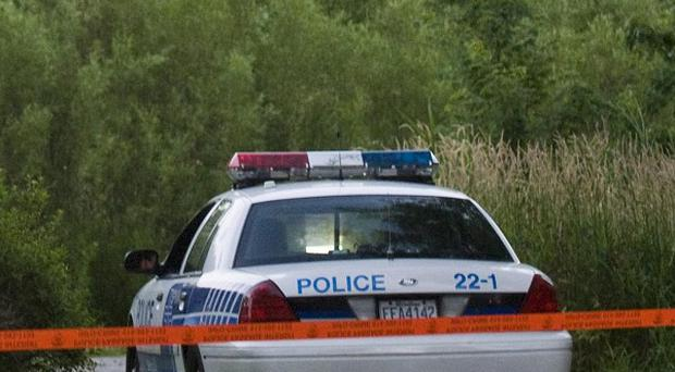 A police vehicle at a Montreal park where police found human remains linked to alleged killer Luka Rocco Magnotta (AP)