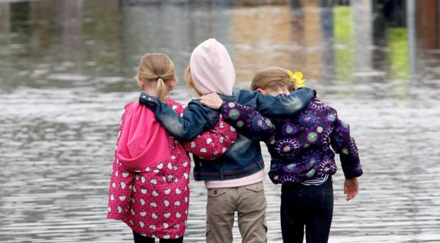 Three young girls take a stroll through the floods on the Mournview Road in Newcastle this morning