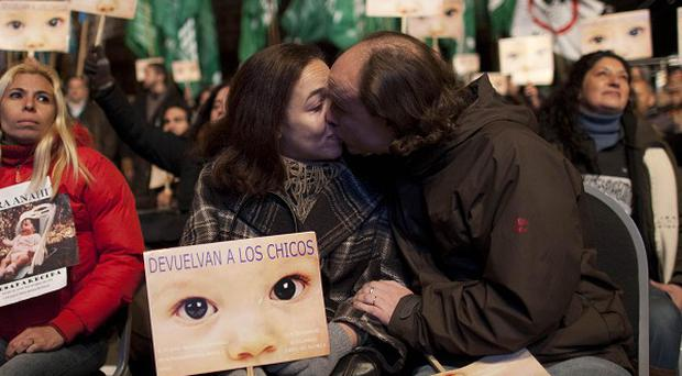 A couple kiss outside a court in Argentina where a trial over stolen babies took place (AP)
