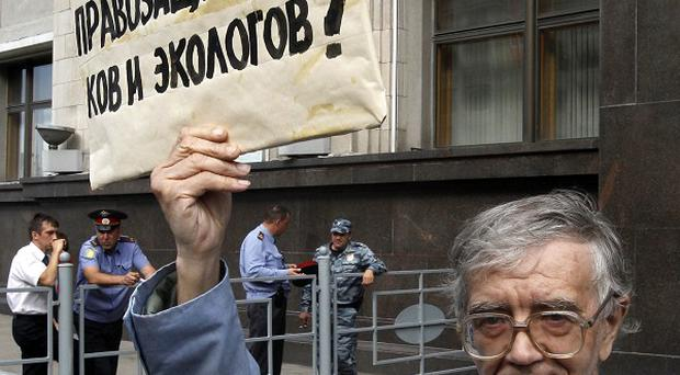 A protester holds a placard reading: 'Who is afraid of human rights activists and ecologists there (in the government)?' outside the Russian parliaments in Moscow (AP)