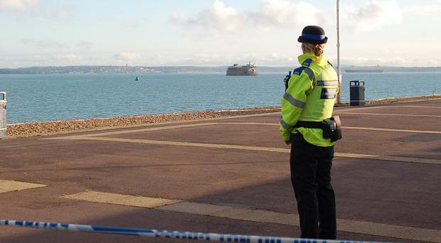 A police officer stands guard near the spot where a torso wrapped in a bin liner was found on a popular tourist beach at Southsea, Hampshire