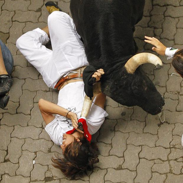 A reveller is tossed by a fighting bull during the running of the bulls of the San Fermin festival, in Pamplona (PA)