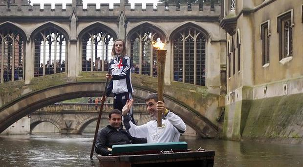 Edward Roberts carrying the Olympic Flame on a punt on the River Cam