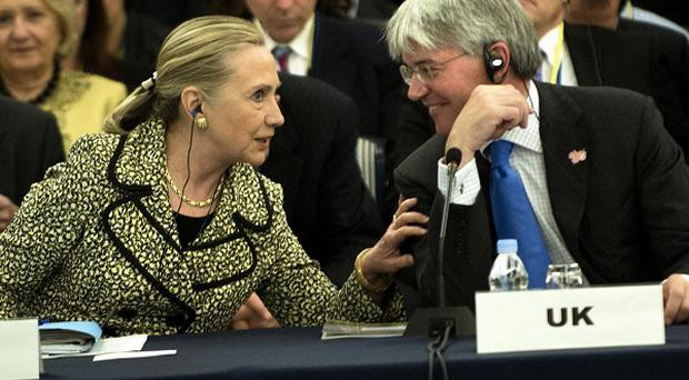US Secretary of State Hillary Clinton speaks with International Development Secretary Andrew Mitchell in Tokyo (AP)