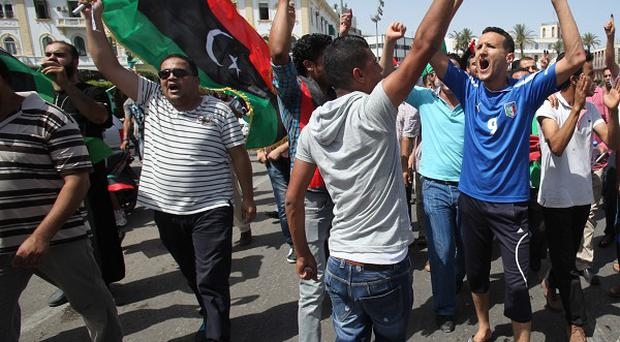 Libyans hold up ink-marked fingers that show they have voted as they celebrate in Tripoli (AP)