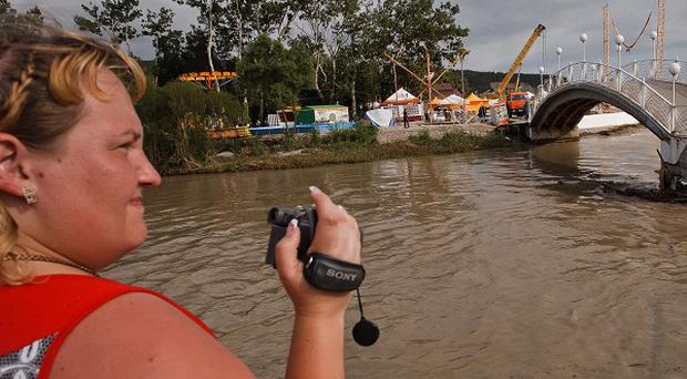A woman takes video of the flood in the Black Sea resort of Gelendzhik, southern Russia (AP)