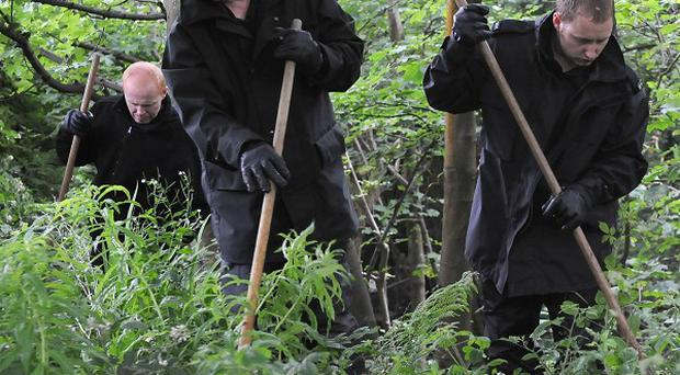 Police carry out a search through woodland in Marsden, near Huddersfield, West Yorkshire, where two men aged 18 and 19 were stabbed