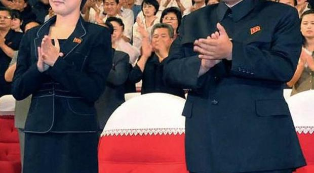 North Korean leader Kim Jong Un and a mystery woman clap as they watch a performance in Pyongyang (AP/Korean Central News Agency via Korea News Service)