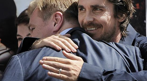 Christian Bale gives Christopher Nolan a hug during the hand and footprint ceremony