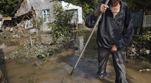 A man at a flooded house in Krymsk in Russia (AP)