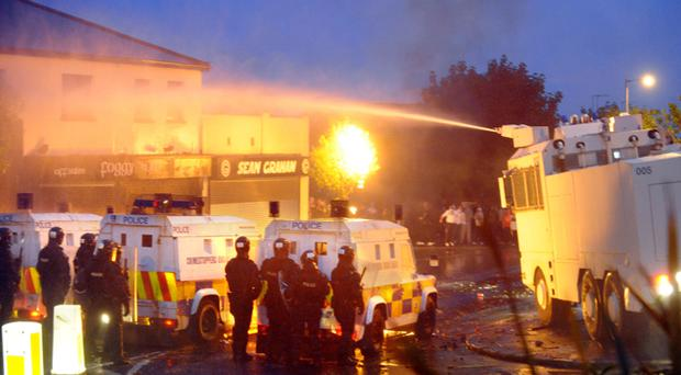 A PSNI water-cannon puts out a fire on the roof of a pub during last night's disturbances in the Ardoyne area of north Belfast July 2010