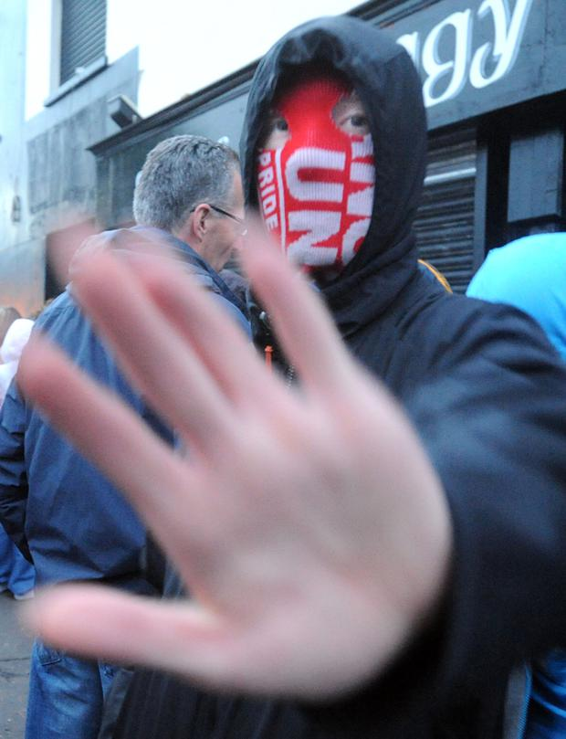 Angry confrontation between Sinn Fein MLA Gerry Kelly (left) and masked youths at Ardoyne shops on a fourth consecutive night of rioting July 2010