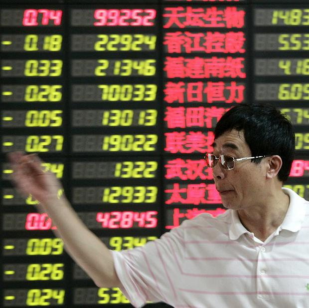 An investor gestures in front of the stock price monitor at a private securities company in Shanghai (AP)
