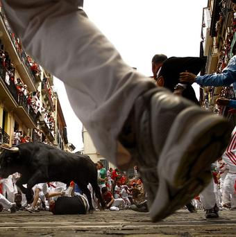 Revelers run in front of a pack of six El Pilar's ranch fighting bulls during the running of the bulls of the San Fermin festival, in Pamplona (AP Photo)