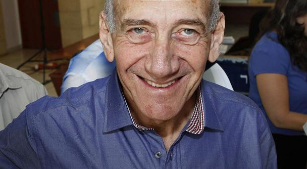 Former Israeli prime minister Ehud Olmert smiles at Jerusalem's District Court following the verdict hearing in his trial (AP)