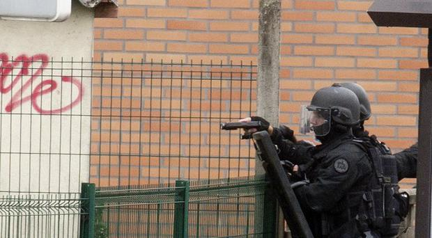A police officer holds a weapon near the Charles Perrault school complex where a man took hostages (AP)