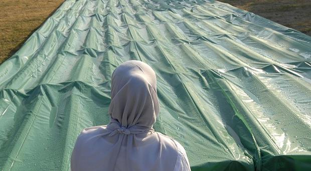 A Bosnian Muslim woman prays in front of the 520 coffins laid out at the Potocari memorial cemetery near Srebrenica (AP)