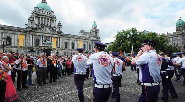 Orangemen and women march towards Belfast City Hall