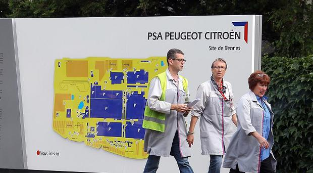 Workers walk past a site map at the PSA Peugeot Citroen La Janais factory near Rennes, western France (AP)