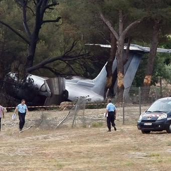 Police officers walk near the plane that crashed on landing at Le Castellet airport, near Toulon (AP)