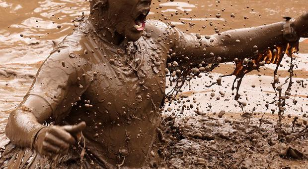 A participant tackles the Mud Mile obstacle during the 2012 Tough Mudder Challenge held in the grounds of Drumlanrig Castle, Dumfriesshire