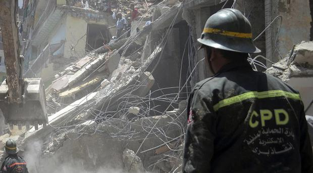 Rescue workers remove rubble and look for survivors after a building collapsed in the Gomrouk area of Alexandria, Egypt (AP)